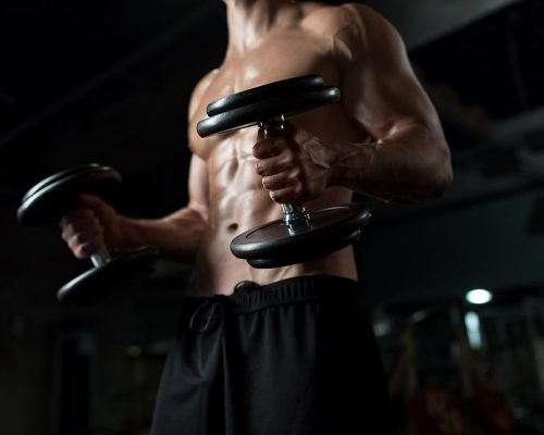 close-up-of-man-with-dumbbells-exercising-in-gym-PNGBLV9-min.jpg